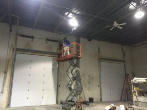 Garage Door Technician standing on top of a scissor lift while repairing a tall steel commercial garage door.