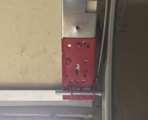 Red garage door hinges with rollers and a cable attached for a garage door to go up and down.