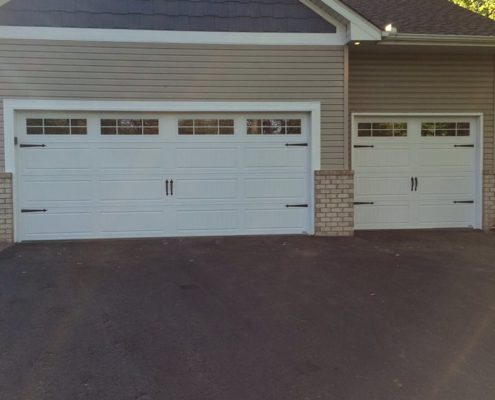 Nice white carriage garage doors with a tan home and brick foundation.