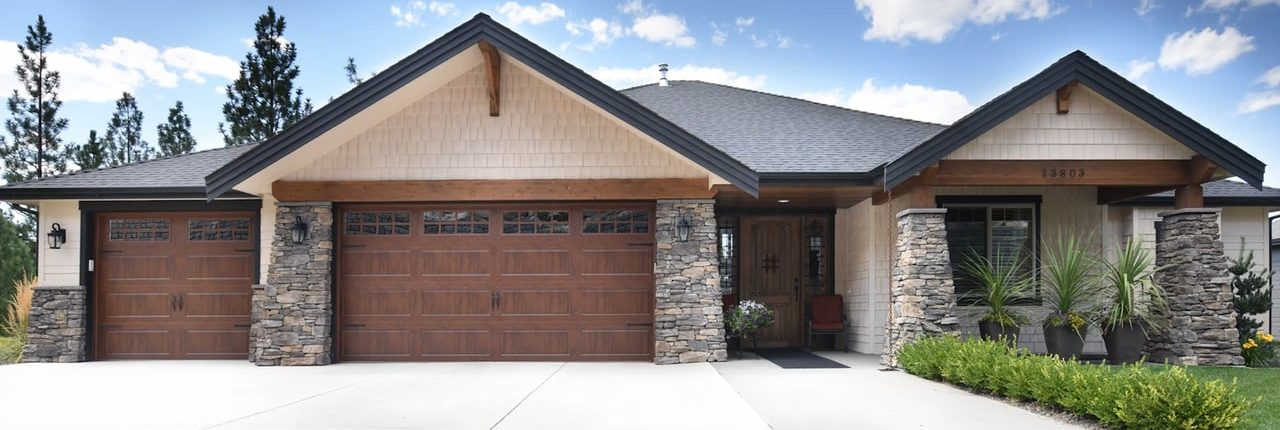 Outside of a house with a brown garage door and beautiful stone pillars holding up the front of the home.